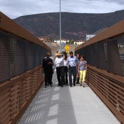 Karen walking across a bridge with community members.