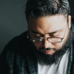 Latinx man looking down. Photo by Hermes Rivera on Unsplash.