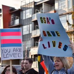 "Two people holding signs: One with the transgender flag with ""You are loved"" and another with a sign reading ""GSA SAVES LIVES"""